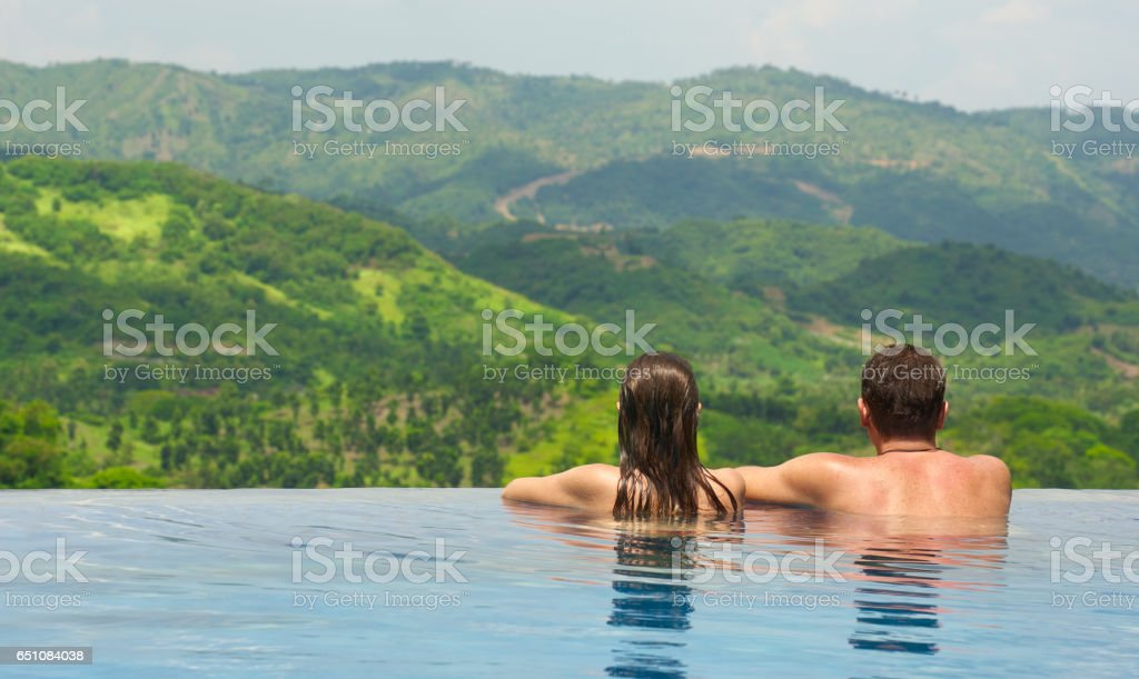 Rear view of couple enjoying the view of the mountain landscape from pool stock photo