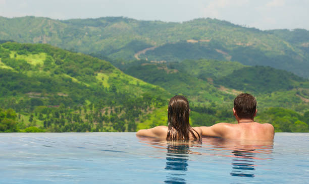 Rear view of couple enjoying the view of the mountain landscape from pool Rear view of happy couple in the pool looking at the mountain landscape. infinity pool stock pictures, royalty-free photos & images