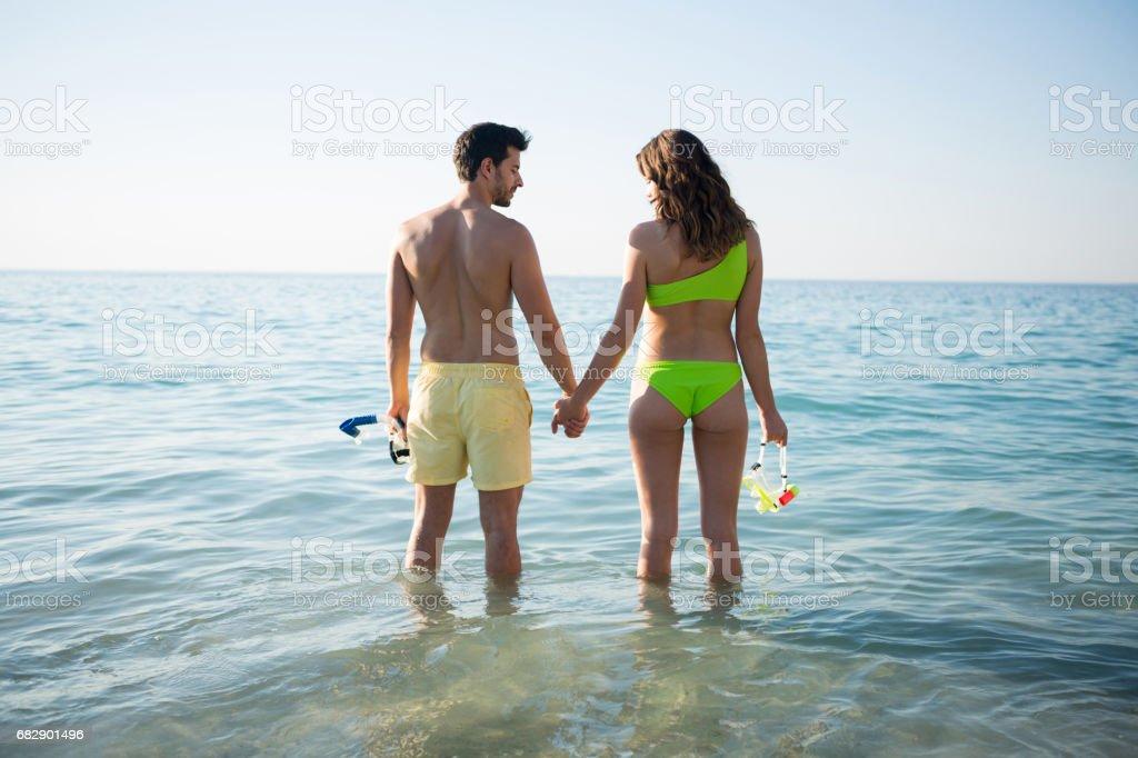Rückansicht des paar Hand in Hand im Meer am Strand Lizenzfreies stock-foto