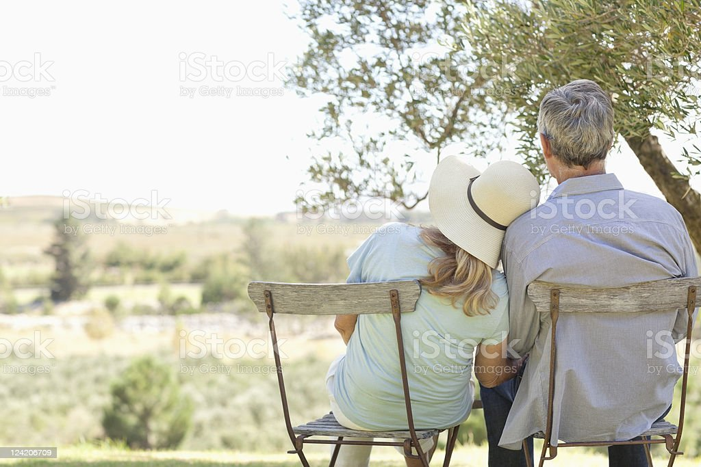 Rear view of couple in chairs at park stock photo