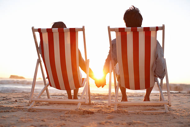 Rear view of couple in deck chairs on beach stock photo