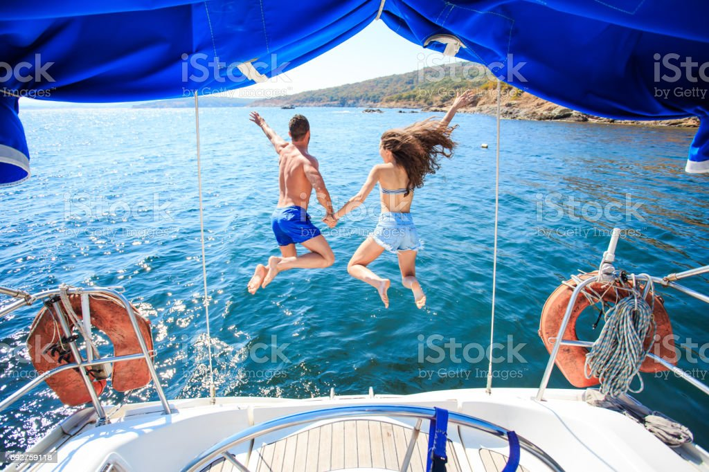 Rear view of couple jumping into ater stock photo