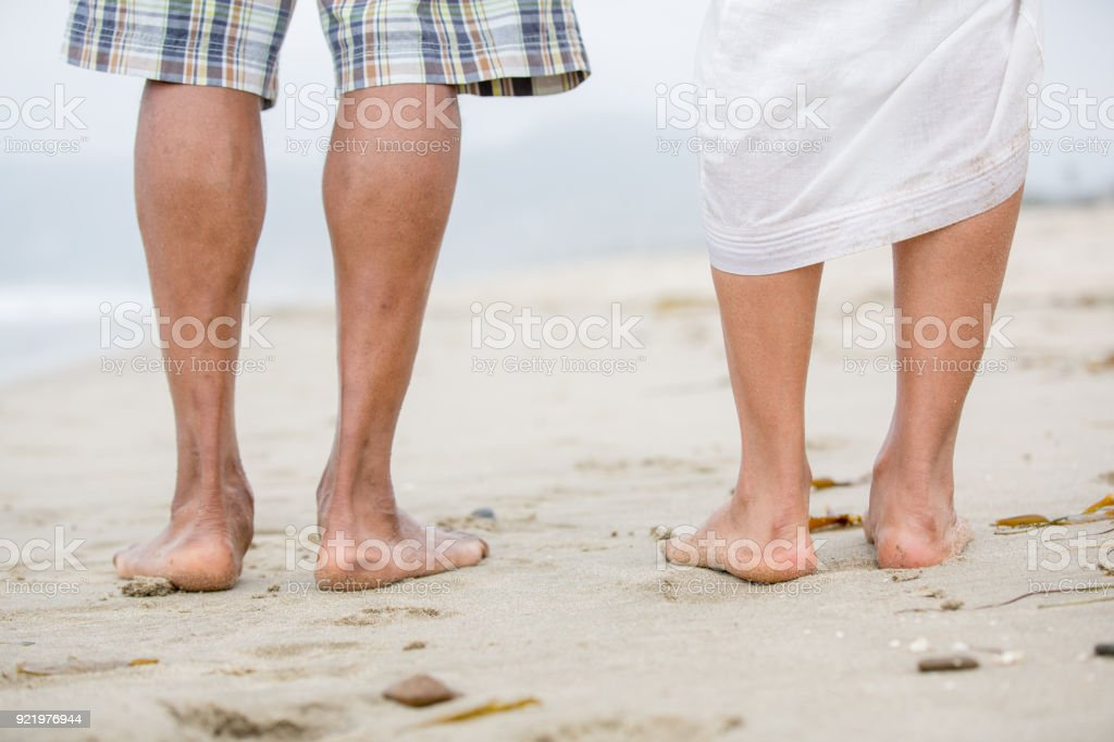 Rear View of Couple Legs Walking on Beach стоковое фото