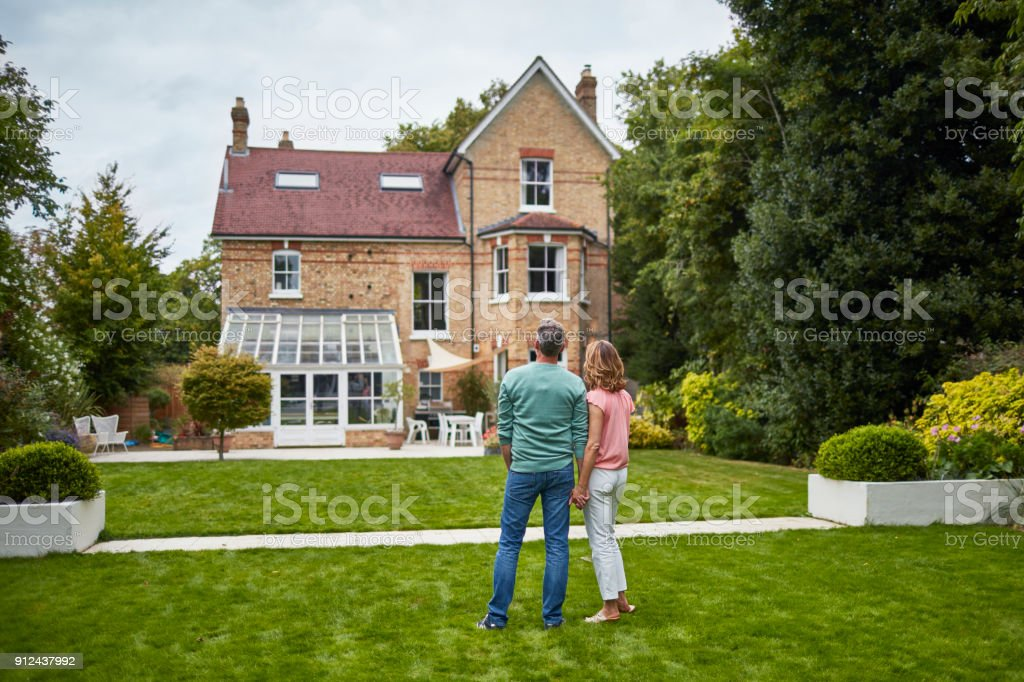 Rear view of couple on grass looking at house stock photo