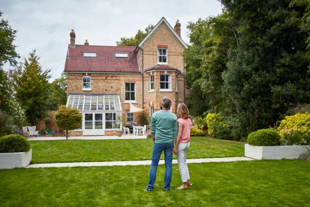 rear view of couple on grass looking at house - people uk stock photos and pictures
