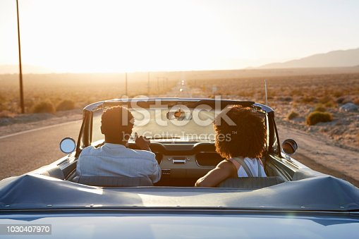 1030408008 istock photo Rear View Of Couple On Road Trip Driving Classic Convertible Car Towards Sunset 1030407970