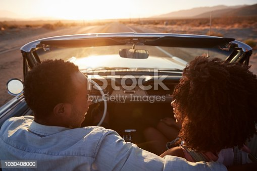 1030408008 istock photo Rear View Of Couple On Road Trip Driving Classic Convertible Car Towards Sunset 1030408000