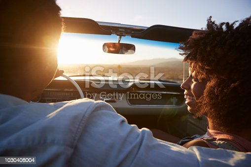 1030408008 istock photo Rear View Of Couple On Road Trip Driving Classic Convertible Car Towards Sunset 1030408004