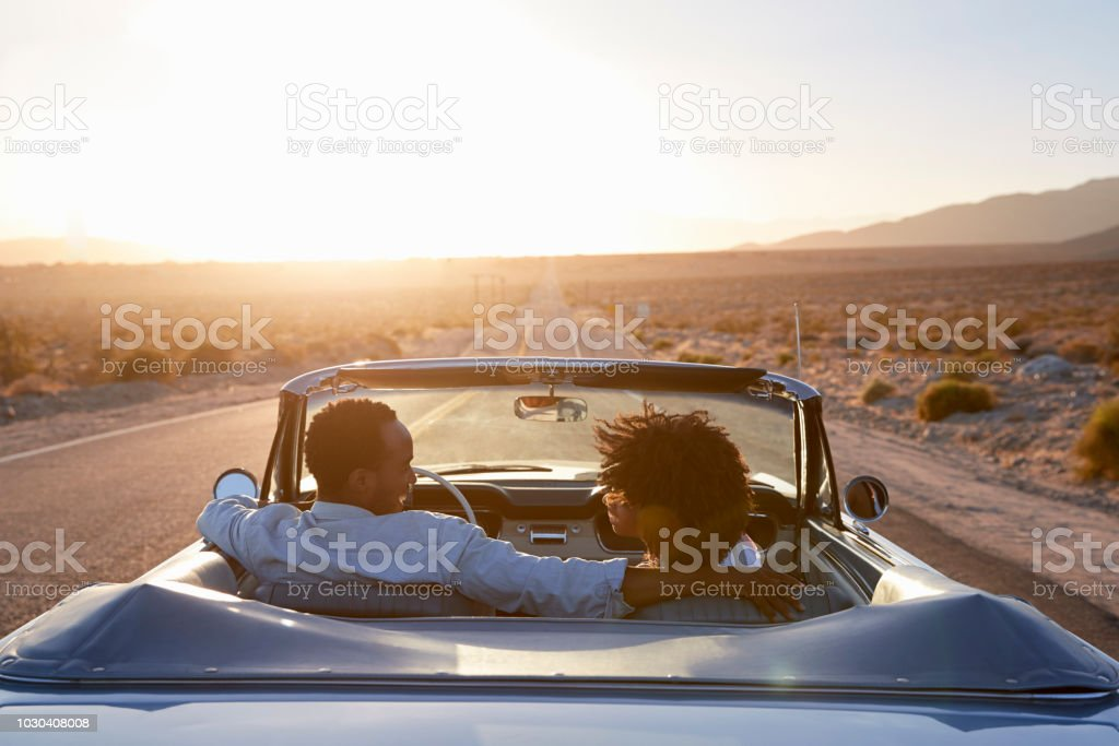 Rear View Of Couple On Road Trip Driving Classic Convertible Car Towards Sunset stock photo