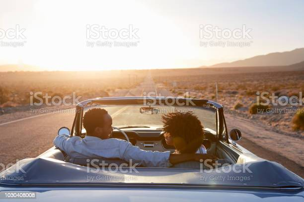 Rear View Of Couple On Road Trip Driving Classic Convertible Car Towards Sunset Stock Photo - Download Image Now