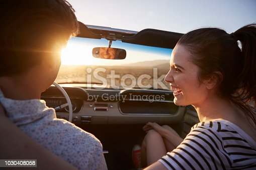 1030408008 istock photo Rear View Of Couple On Road Trip Driving Classic Convertible Car Towards Sunset 1030408058