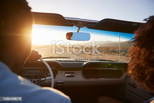 1030408008 istock photo Rear View Of Couple On Road Trip Driving Classic Convertible Car Towards Sunset 1030408076