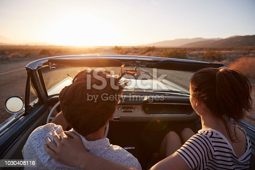 1030408008 istock photo Rear View Of Couple On Road Trip Driving Classic Convertible Car Towards Sunset 1030408116