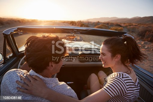 1030408008 istock photo Rear View Of Couple On Road Trip Driving Classic Convertible Car Towards Sunset 1030408146