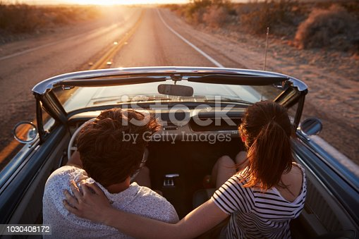 1030408008 istock photo Rear View Of Couple On Road Trip Driving Classic Convertible Car Towards Sunset 1030408172
