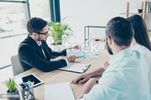 istock Rear view of couple sitting in the brunet`s smart lawyer`s work station,  discussing the possibility f taking credit for buying purchase, all are dressed in formal outfits 935664580