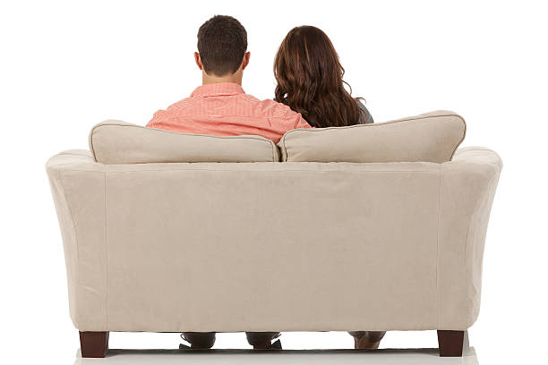 Rear view of couple sitting on a couch stock photo