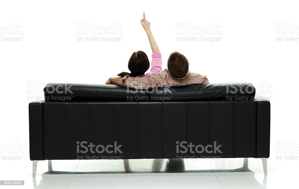 Rear view of couple sitting on couch stock photo