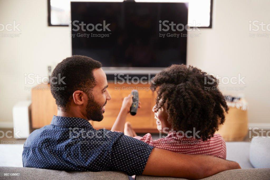Rückansicht des Paares auf Sofa vor dem Fernseher zusammen sitzen – Foto