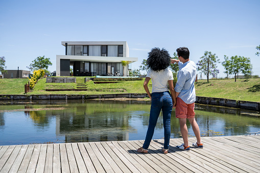 Rear view of couple standing on pier by lake looking at house
