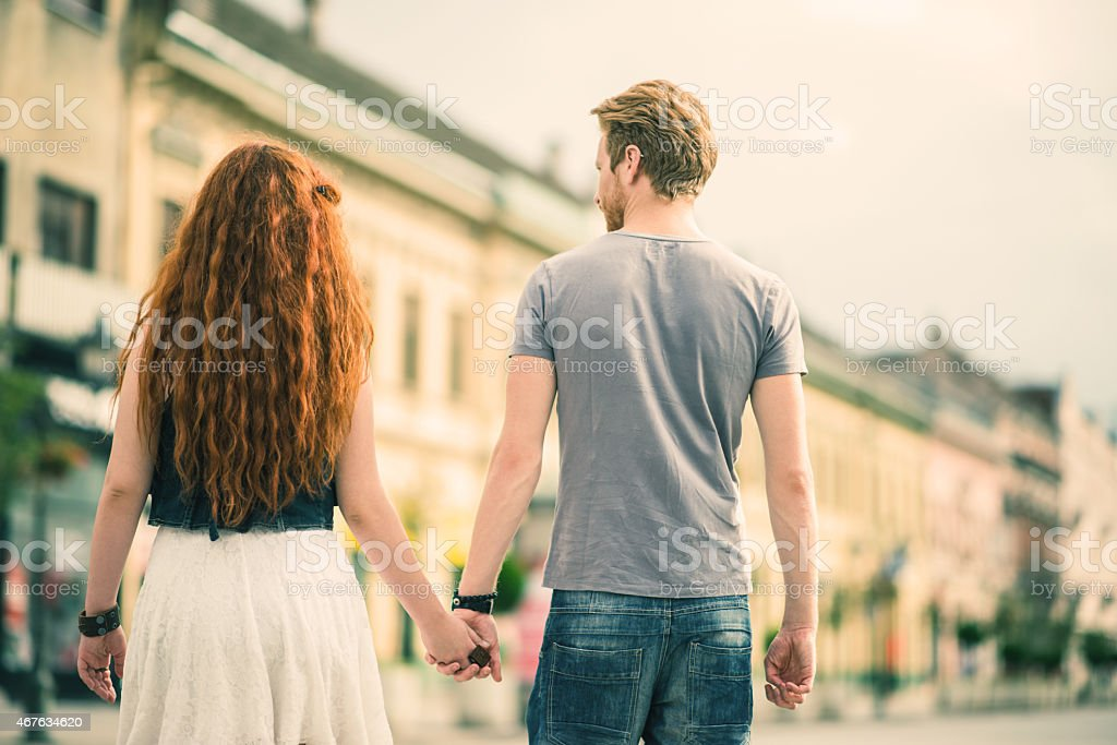 Rear view of young ginger couple walking in the street while holding...