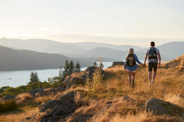 Rear View Of Couple Walking On Top Of Hill On Hike Through Countryside In Lake District UK Rear View Of Couple Walking On Top Of Hill On Hike Through Countryside In Lake District UK english lake district stock pictures, royalty-free photos & images