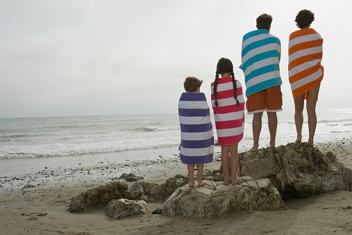 Rear view of couple with two children wrapped in towels