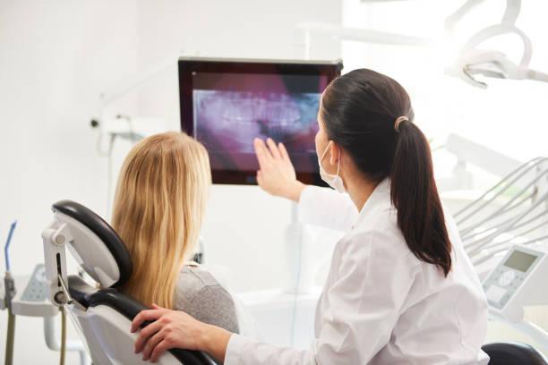 bak sida av tandläkare och patient tittar på röntgen bild - two dentists talking bildbanksfoton och bilder