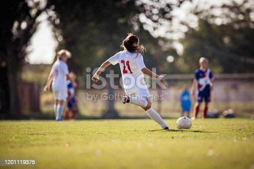 Back view of female soccer player kicking the ball during a match on a stadium.