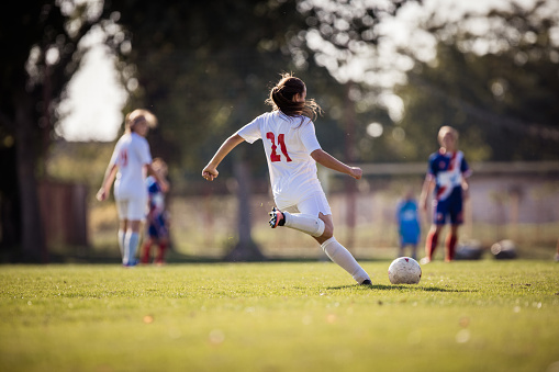 Rear view of determined female soccer player kicking the ball on a match.