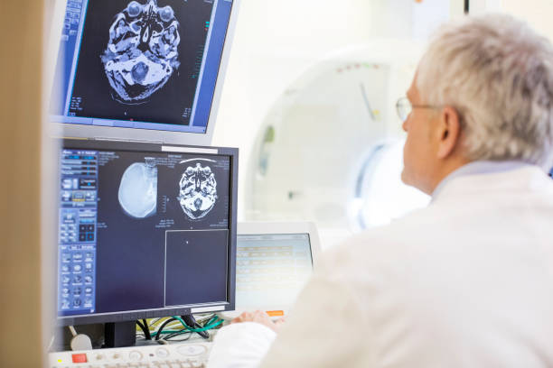 Rear view of doctor examining CAT scan reports stock photo