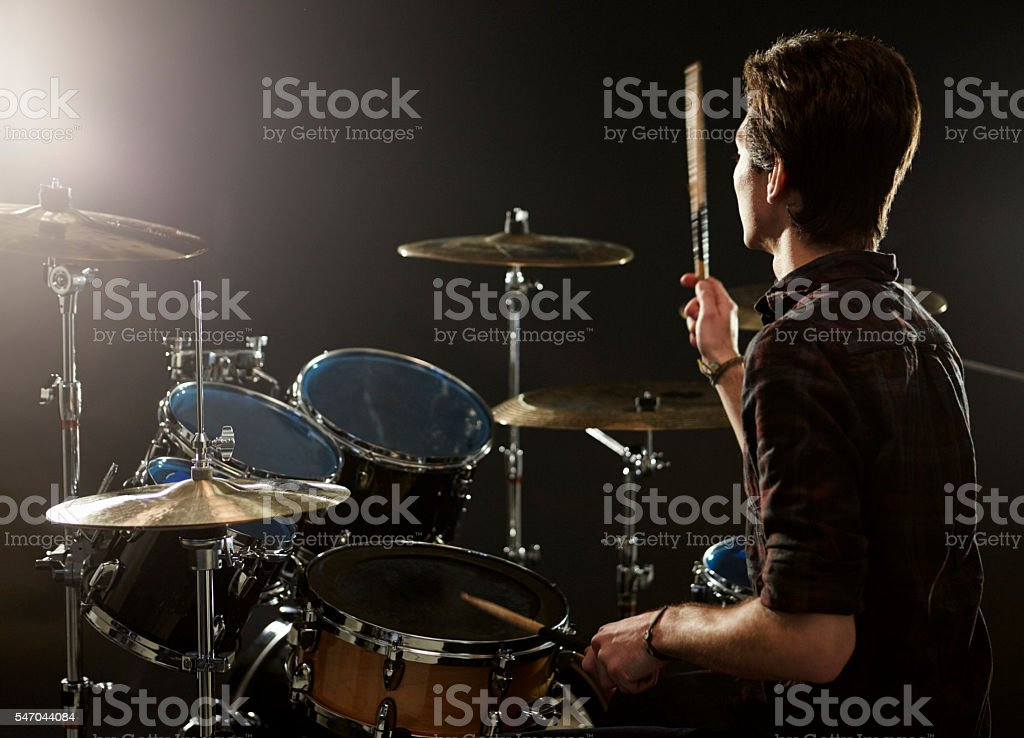 Rear View Of Drummer Playing Drum Kit In Studio stock photo