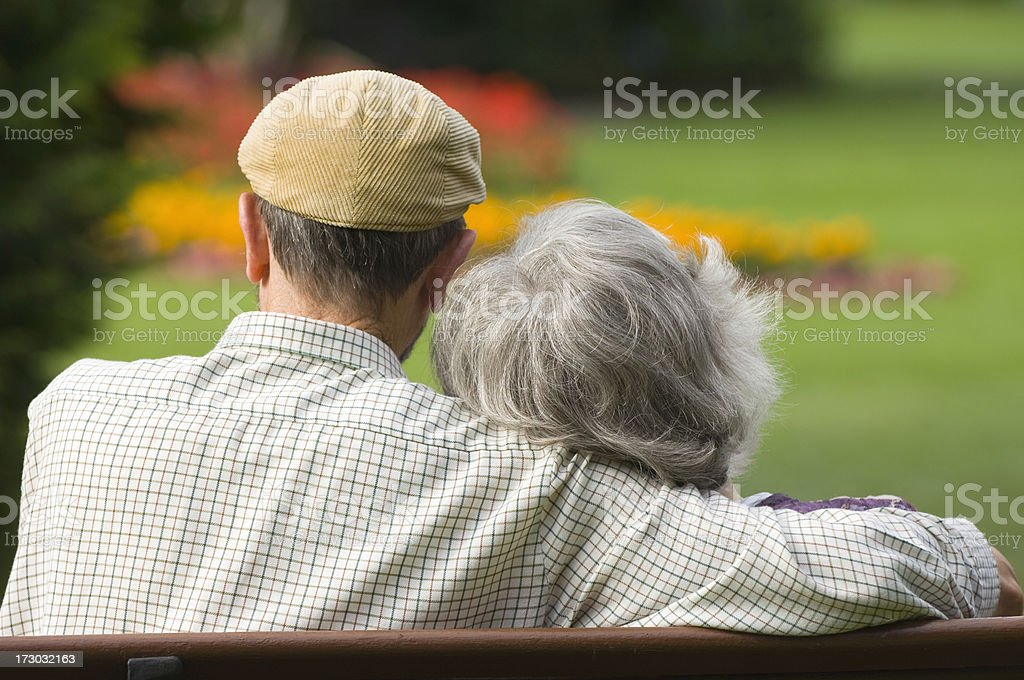 Rear view of elderly man with arm around woman sat on bench royalty-free stock photo