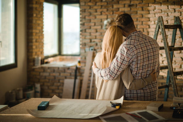 Rear view of embraced couple at construction site of their apartment. stock photo