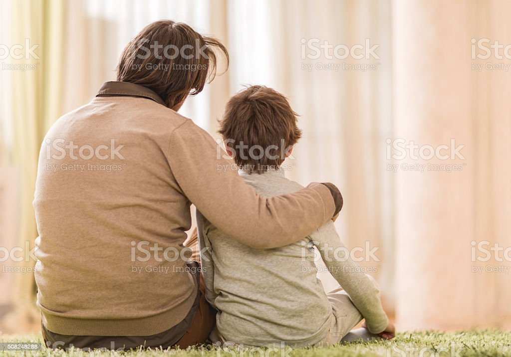 Back view of father embracing his son while sitting on the carpet at...