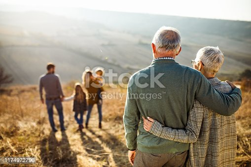 Back view of embraced grandparents enjoying while looking at their family on a field in autumn day.