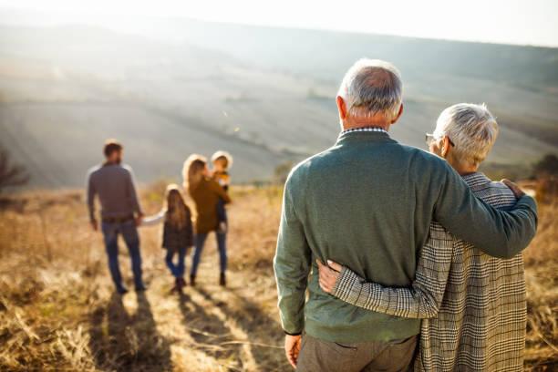 vista posteriore della coppia senior abbracciata che guarda la loro famiglia nella natura. - family foto e immagini stock
