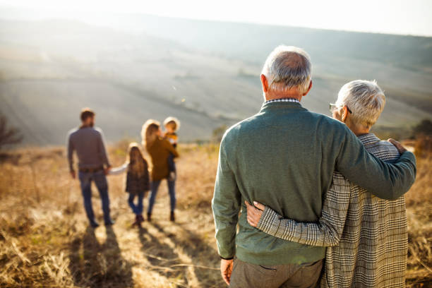 Rear view of embraced senior couple looking at their family in nature. stock photo