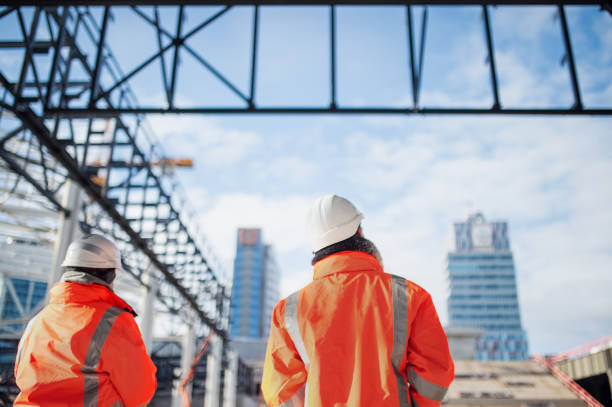 Rear view of engineers standing outdoors on construction site. stock photo