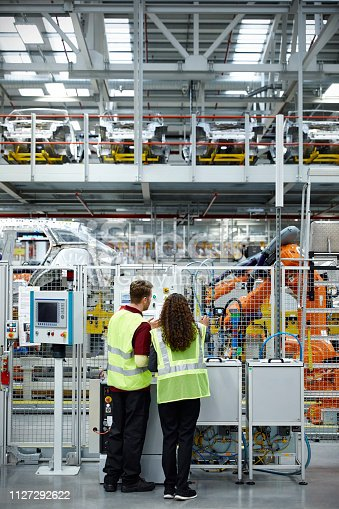istock Rear view of engineers working in car plant 1127292622