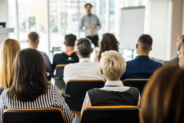 Rear view of entrepreneurs attending a business seminar in board room. stock photo