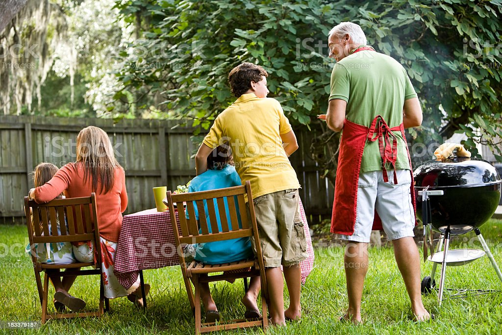 Rear view of family backyard barbeque royalty-free stock photo
