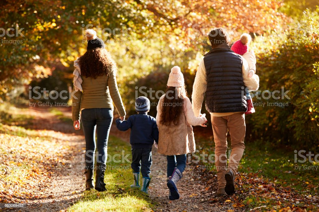 Rear View Of Family Enjoying Autumn Walk In Countryside stock photo