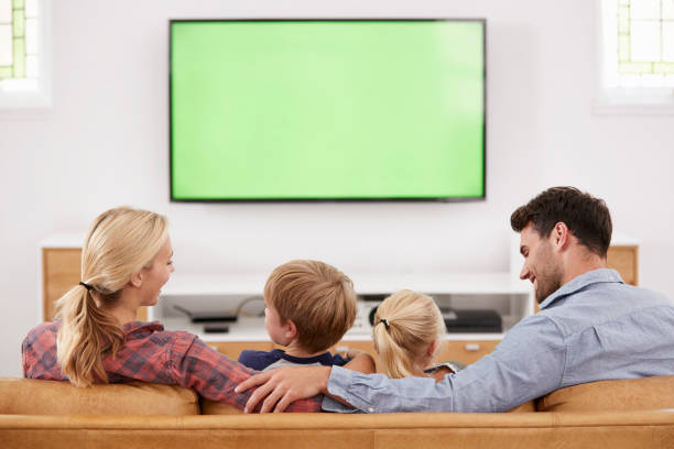 Rear View Of Family Sitting On Sofa In Lounge Watching Television stock photo