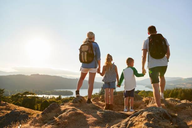 vista posterior de la familia en la cima de la colina en caminata por campo en reino unido del distrito de los lagos - excursionismo fotografías e imágenes de stock