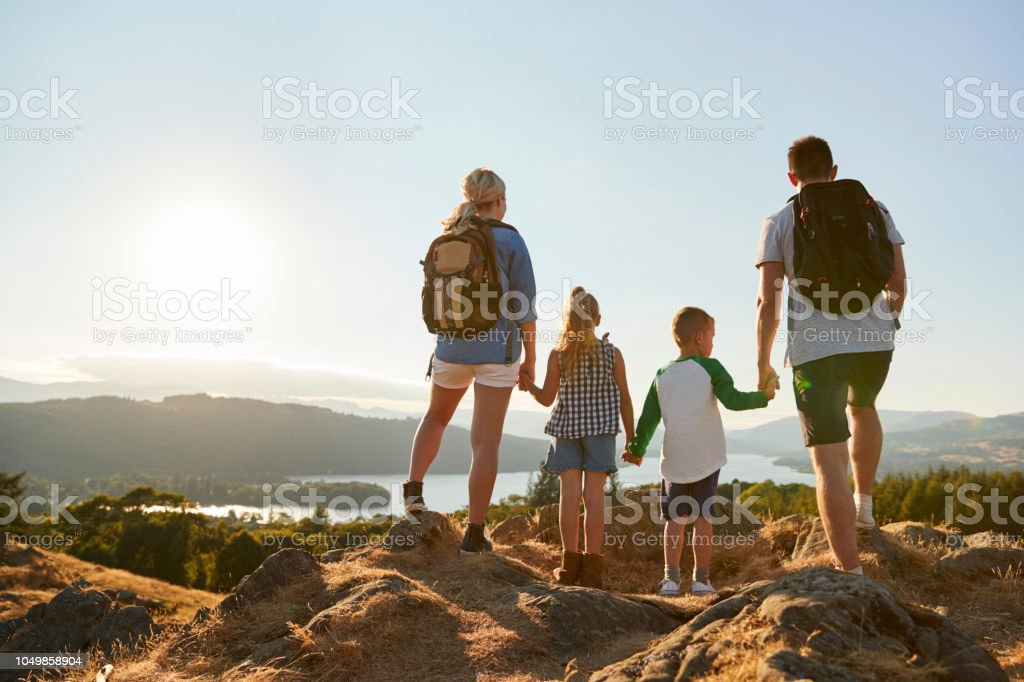 Rear View Of Family Standing At Top Of Hill On Hike Through Countryside In Lake District UK stock photo