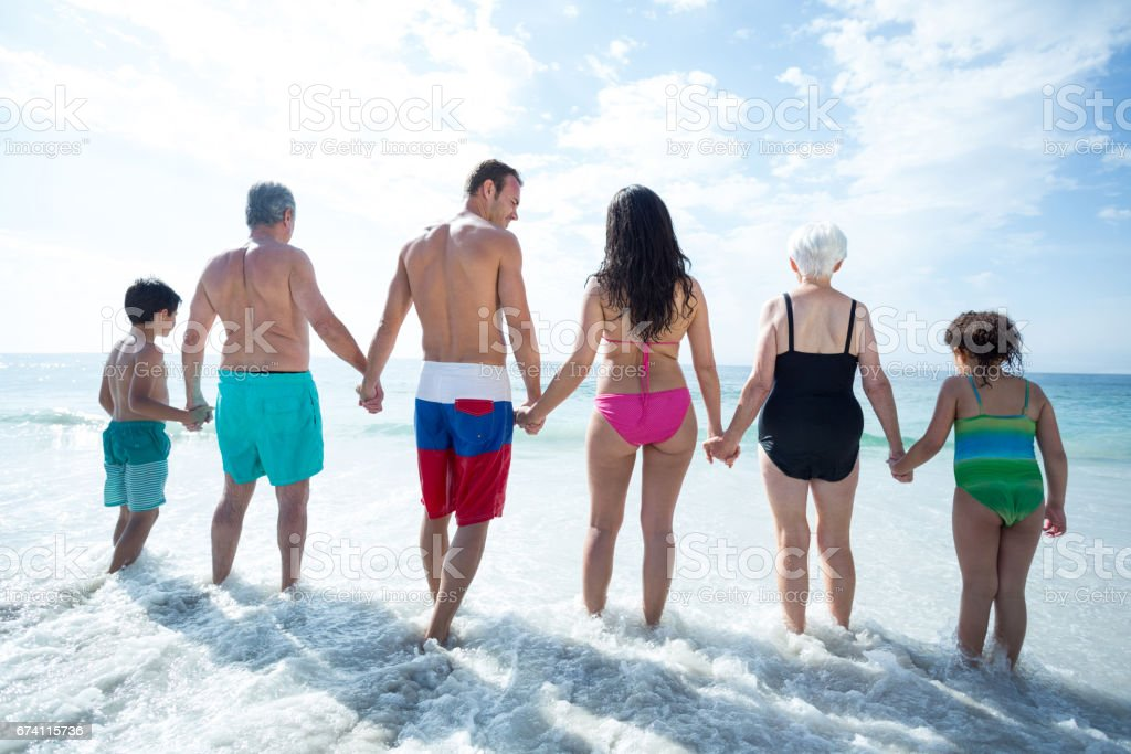 Rear view of family walking at beach royalty-free stock photo