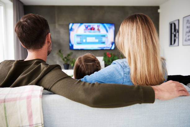Rear view of family watching tv in living room stock photo