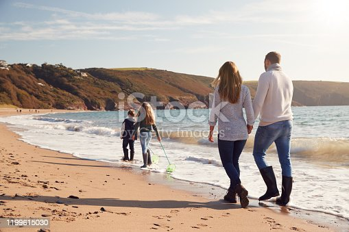 istock Rear View Of Family With Fishing Nets Walking Along Shoreline Of Winter Beach 1199615030