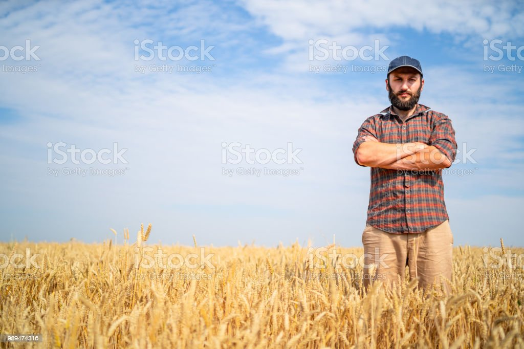 Rear view of farmer standing with arms crossed in the middle of field
